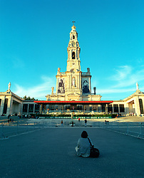 Pilgrim sits in the square of the Roman Catholic Cathedral of Fatima in Portugal.