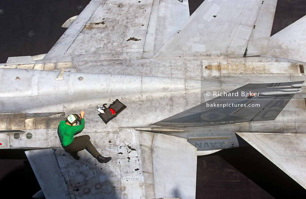 A lone deck hand sailor repairs a grubby F/A-18C Hornets fighter jet on the aircraft carrier USS Harry S Truman. The Truman is the largest and newest of the US Navy's fleet of new generation carriers, a 97,000 ton floating city with a crew of 5,137, 650 are women.