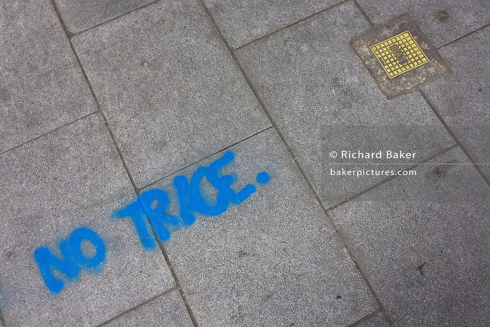 The words No Trace has been sprayed in aerosol on a London pavement near a gas utility outlet cover.