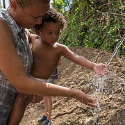 OCTOBER 25 - UTUADO, PUERTO RICO - <br /> Paola Bernacett, 19, carries Darian Santos, 1, as he touches water  from a stream of coming from a mountain in Utuado.<br /> (Photo by Angel Valentin/Freelance)