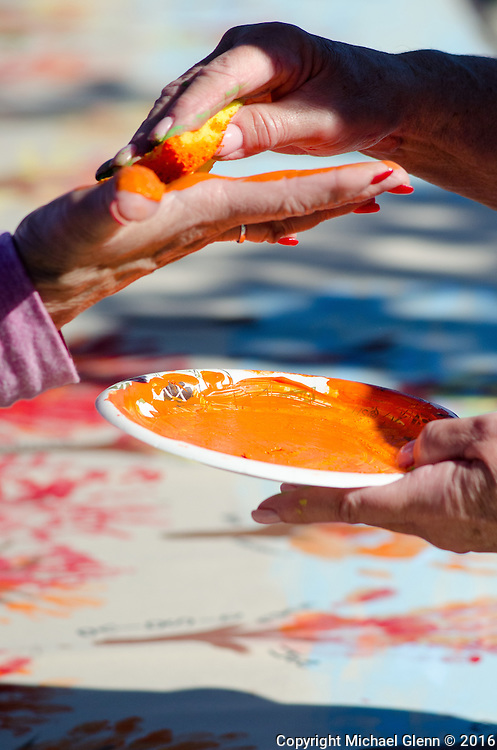 15 Oct. 2016 Forked River USA / Volunteer paints the hand of a woman, hands are then placed on the family mural and the paint is pressed into the fabric as St Pius X celebrates it's 10th year in their new church with a festival open to all  /  Michael Glenn  / Glenn Images