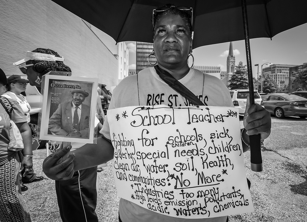 """Stephanie Cooper, the Vice President of Rise St. James  holding a photo of her father who died of cancer on the final day of a five day march through Louisiana's 'Cancer Alley' .. The march, held by the Coalition Against Death Alley. The Coalition Against Death Alley (CADA), is a group of Louisiana-based residents and members of various local and state organizations, is calling for a stop to the construction of new petrochemical plants and the passing of stricter regulations on existing industry in the area that include the groups RISE St. James, Justice and Beyond, the Louisiana Bucket Brigade, 350 New Orleans, and the Concerned Citizens of St. John. Louisiana's Cancer Alley, an 80-mile stretch along the Mississippi River, is also known as the """"Petrochemical Corridor,"""" where there are over 100 petrochemical plants and refineries ."""