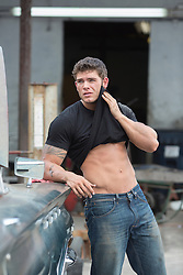 very good looking muscular auto mechanic wiping dirt off his face with his tee shirt