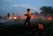 Firefighters douse a fire that was burning through a field and debris pile in Star near the intersection of Brandon and New Hope, north of Floating Feather. The fire threataned several residences in the area. Residents reported that the fire started from a downed power line caused by a wind storm.
