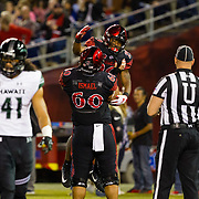 24 November 2018: San Diego State Aztecs running back Juwan Washington (29) celebrates with teammate Keith Ismael (60) after rushing the ball for a two yard touchdown to give the Aztecs a 14-3 lead in the first quarter. The Aztecs closed out the season with a 31-30 overtime loss to Hawaii at SDCCU Stadium.