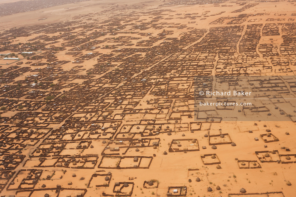 Aerial view of Al Fasher (also spelled, Al-Fashir) the front-line town in north Darfur. Basic housing is seen against the barren and scorched red earth in this area of south-western Sudan. ..