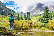 Lee Erb casts for trout at the edge of Maroon Lake as the fall colors begin to shine through in the background in Aspen, Colorado.