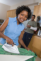 Mid-adult couple at domestic kitchen, woman ironing