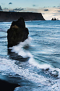 A wave breaks around a basalt sea stack in the waters off of Iceland's Black Sand Beach.