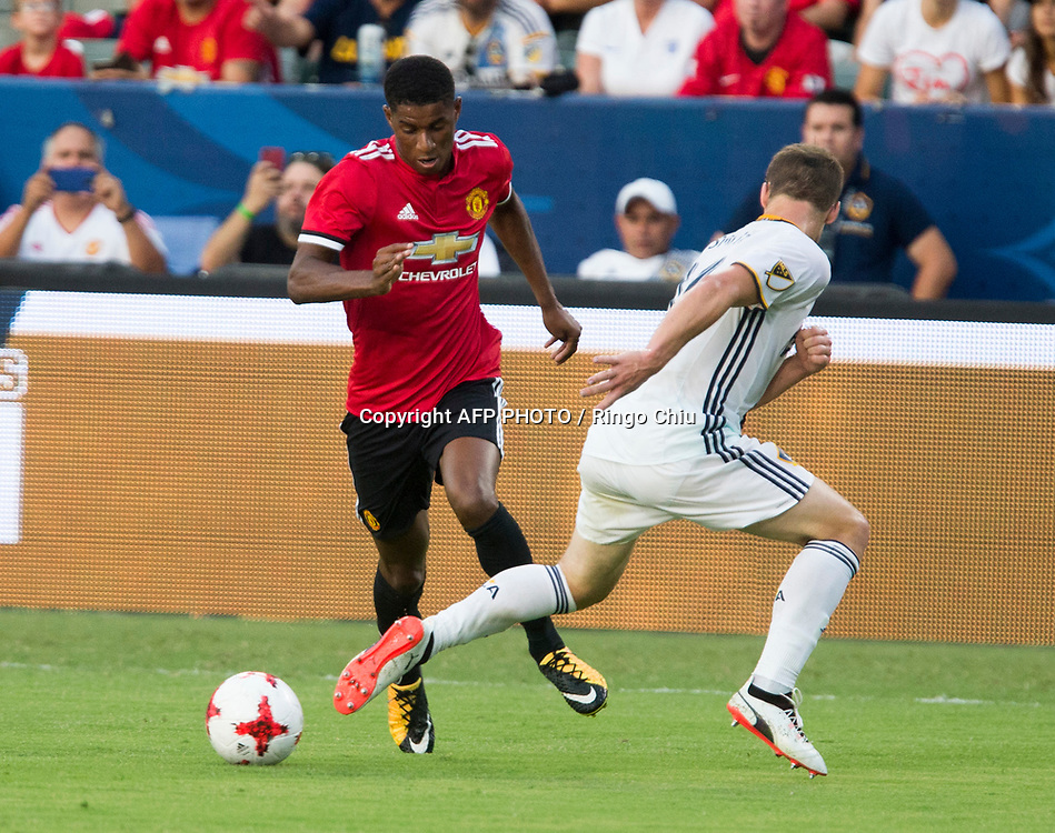 Los Angeles Galaxy midfielder , left, and Manchester United defender  battle for the ball during the first half of a national friendly soccer game at StubHub Center on July 15, 2017 in Carson, California.   AFP PHOTO / Ringo Chiu