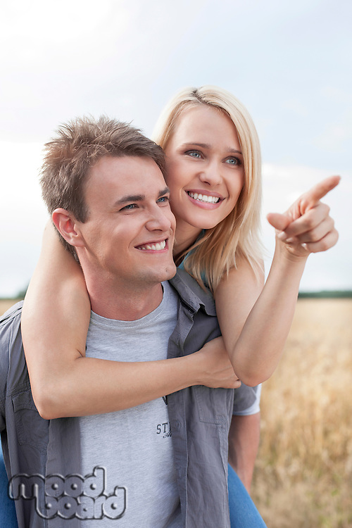 Happy woman showing something to man while enjoying piggyback ride at field