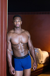 muscular black man in his underwear standing in a bedroom doorway