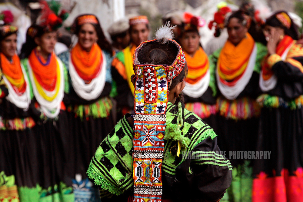 "KALASHA VALLEYS, PAKISTAN - MAY 16: A Kalash girl watches women dance in a circle during the ""Joshi"" (spring) festival in the village of Batrik May 16, 2008 in the Kalasha Valleys, northwestern Pakistan. The Joshi Festival is a celebration of dance, music and prayer to welcome the coming of warmer season and the new life and crops it brings. The shrinking Kalash community of 4000, who claim to be descendants of Alexander the Great and worship several gods, are considered by many Pakistanis to be unclean, lazy and heretics. They often face ridicule and persecution for their polytheistic religion and fear the spread of hard-line Islamism bordering their communities. (Photo by Warrick Page)"