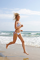 Young woman in bikini running on beach portrait side view