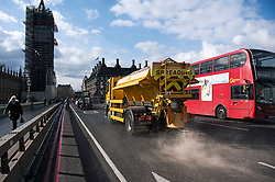 © Licensed to London News Pictures. 26/02/2018. London, UK. A glitter is seen spreading grit on Westminster Bridge, in front of the Houses of Parliament in central London, as a cold front sweeps in from the east. Up to 20cm of snow are expected in parts of the UK, with temperatures feeling as low as -15C in some places. Photo credit: Ben Cawthra/LNP