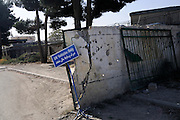 The UN entrance to Kabul International Airport scared by bullet holes from past conflicts.