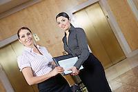Two business women in office corridor, portrait