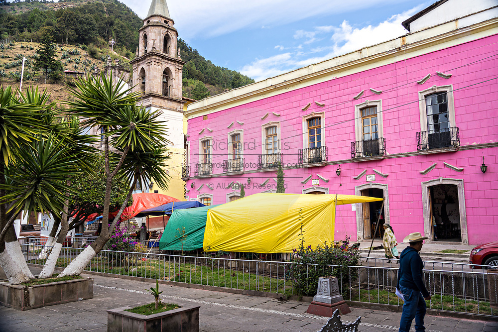 The Parroquia de San Simón Apostol and the pink Hotel Jardin on the Plaza de la Constitucion in Angangueo, Michoacan, Mexico. Angangueo is a tiny, remote mountain town and the entry point to the Sierra Chincua Monarch Butterfly Sanctuary.