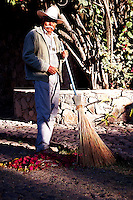 Sweeper poses with broom in early morning sunlight, Ajijiic Mexico