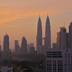Petronas Towers rise above the city of Kuala Lumpur, Malaysia at sunrise.