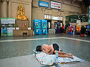 11 JULY 2011 - BANGKOK, THAILAND:  A passenger sleeps on the floor while she waits for her train at Hua Lamphong station in Bangkok. Hua Lamphong Grand Central Railway Station, officially known as the Bangkok Grand Central Terminal Railway Station, is the main railway station in Bangkok, Thailand. It is located in the center of the city in Pathum Wan District, and is operated by the State Railway of Thailand. The station was opened on 25 June 1916, after six years' construction. The station was built in an Italian Neo-Renaissance style, with decorated wooden roofs and stained glass windows. The architecture is attributed to Turin-born Mario Tamagno, who, with countryman Annibale Rigotti made a mark on early 20th century public building in Bangkok. The pair also designed Bang Khun Prom Palace (1906), Ananda Samakhom Throne Hall in The Royal Plaza (1907-15) and Suan Kularb Residential Hall and Throne Hall in Dusit Garden, among other buildings..There are 14 platforms and 26 ticket booths. Hua Lamphong serves over 130 trains and approximately 60,000 passengers each day. Thailand has the most advanced rail system in Southeast Asia and trains from Hua Lamphong serve all corners of the Kingdom.       PHOTO BY JACK KURTZ