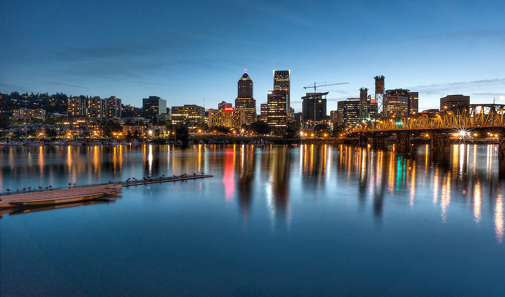 dramatic Cityscape of Portland Oregon skyline with Willamette river in foreground. Camera facing west at sunset.