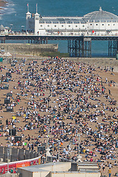 © Licensed to London News Pictures. 18/04/2018. Brighton, UK. Brighton beach seen from the BA I360 viewing attraction. Members of the public take to the beach in Brighton and Hove as sunny and warmer weather continues to hit the seaside resort. Photo credit: Hugo Michiels/LNP