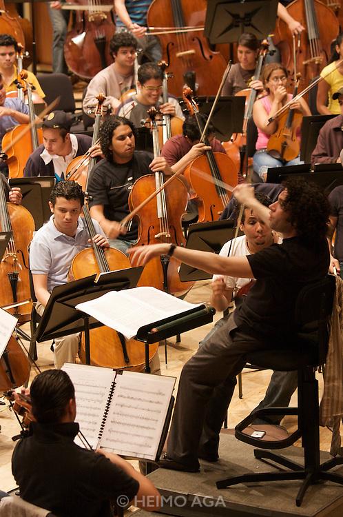 "Simo?n Boli?var Youth Orchestra of Venezuela (SBYOV), rehearsing with its Music Director, conductor Gustavo Dudamel, at the auditorium ""Simo?n Boli?var"" of the ""Centro Latinoamericano de Accio?n Social por la Mu?sica (Center for Social Action Through Music)"". The ""Fundacion del Estado para el Sistema Nacional de las Orquestas Juveniles e Infantiles de Venezuela"" (FESNOJIV, National Network of Youth and Children Orchestras of Venezuela), also known as El Sistema, is a publicly financed private-sector music-education program in Venezuela, originally called Social Action for Music, founded 1975 by Venezuelan economist and amateur musician Jose? Antonio Abreu."