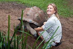 A female zoo worker smiling next to a Aldabran Giant Tortoise (Aldabrachelys gigantea), The Australia Zoo, Beerwah, Queensland, Australia