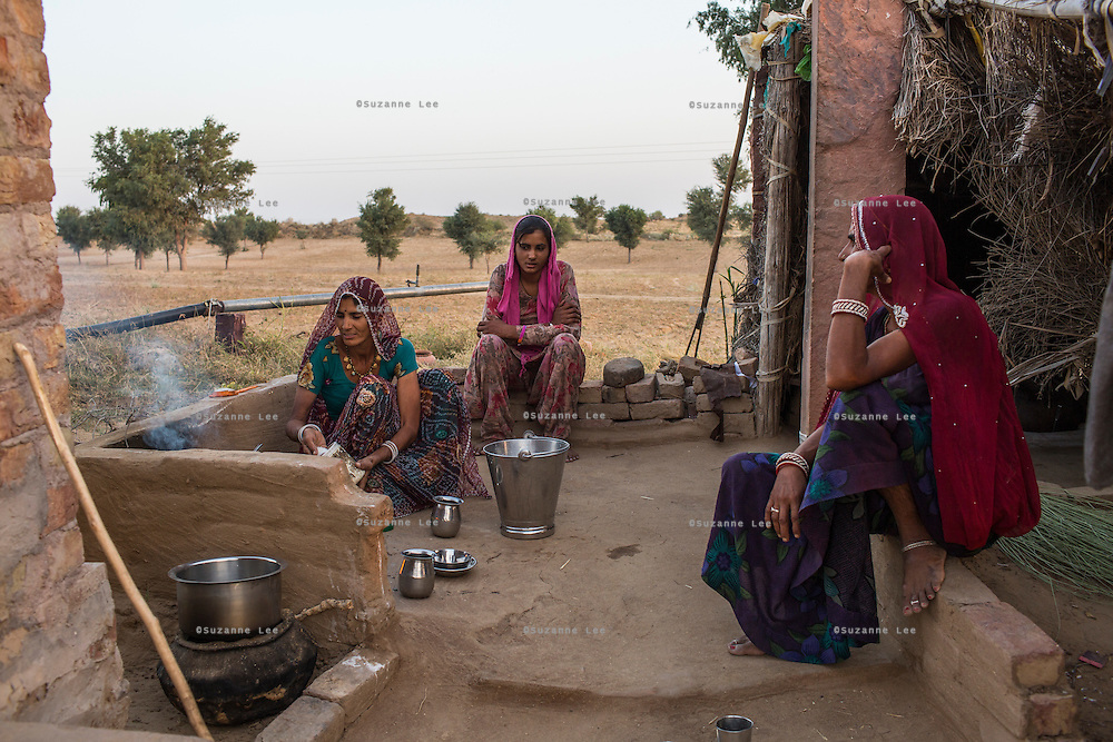 Guar farmer Kelavati Devi (left), 38, makes tea for her family after a hard day's work in their field in Rajera village, Bikaner, Rajasthan, India on October 23, 2016. Non-profit organisation Technoserve works with farmers in Bikaner, providing technical support and training, causing increased yield from implementation of good agricultural practices as well as a switch to using better grains better suited to the given climate. Photograph by Suzanne Lee for Technoserve