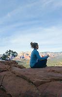 Woman meditating on rock.
