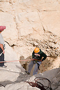 Israel, Dead Sea, Qumran, Group rappeling down a dry waterfall of the Qumran river