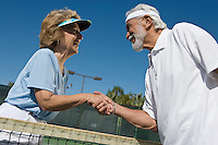 Man and woman shaking hands over tennis net
