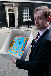 © licensed to London News Pictures. London, UK  10/5/11 Reporter from the Daily Politics show Adam Fleming poses for a cameraman with a cake to celebrate the 1st Anniversary of the coalition Please see special instructions for usage rates. Photo credit should read OLIVIA HARRIS/LNP