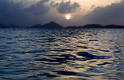 Wave Cresting in the Caribbean sea, in Solomon Bay, Saint John, Virgin Islands with a view of the sun setting over Saint Thomas, Virgin Islands in the background.