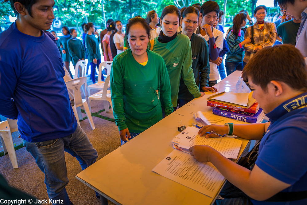 "17 JULY 2014 - BANGKOK, THAILAND:  Undocumented Cambodian construction workers sign up for temporary ID cards at the temporary ""one stop service center"" in the Bangkok Youth Center in central Bangkok. Thai immigration officials have opened several temporary ""one stop service centers"" in Bangkok to register undocumented immigrants and issue them temporary ID cards and work permits. The temporary centers will be open until August 14.   PHOTO BY JACK KURTZ"