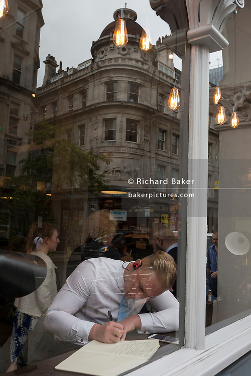 A young man concentrates on writing in a notebook in the window of a City of London cafe, on 4th June 2018, in London, England.