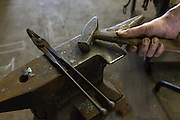 Blacksmiths hands on a hammer and anvil in a metal working shop in Charleston, SC