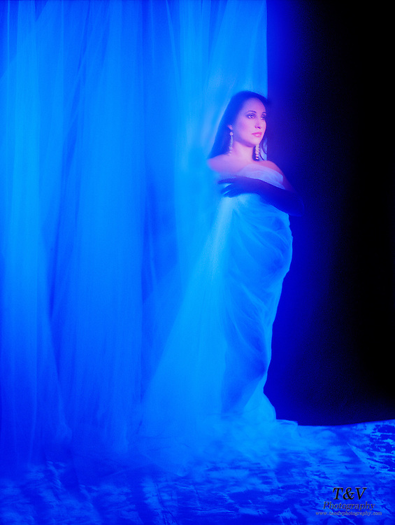 Pregnant woman standing on blue tarp, surrounded by glowing veil.Black light