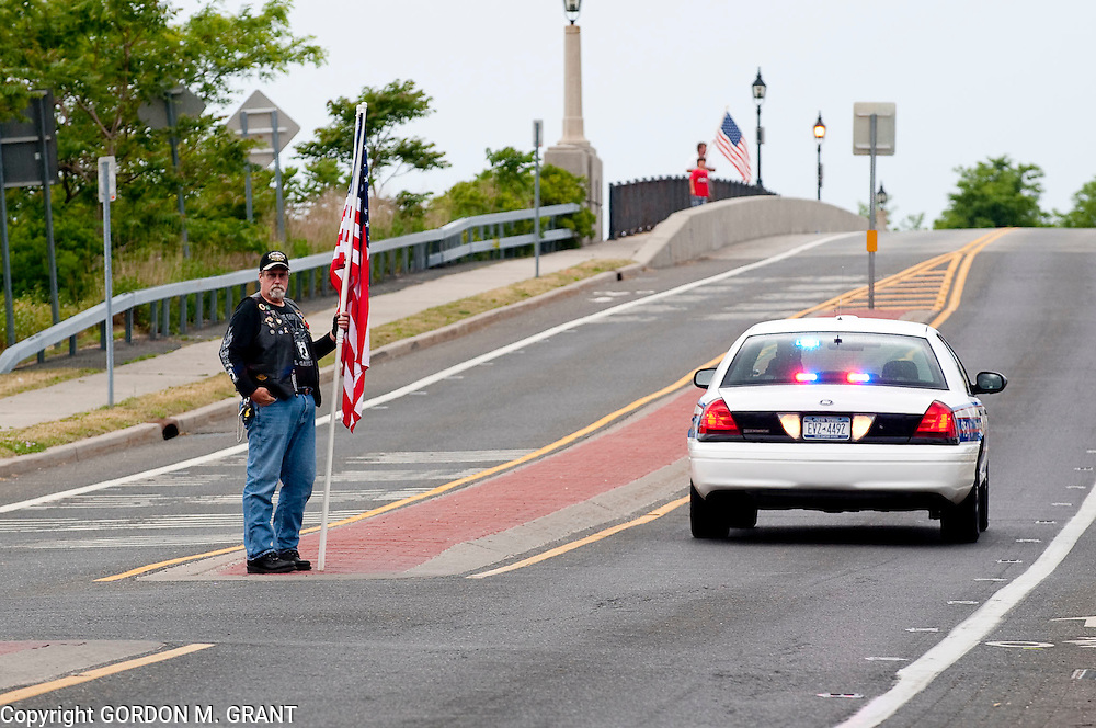 A man with a flag stands at the base of the Lance Cpl. Jordan Haerter Veterans' Memorial Bridge in Sag Harbor waiting for the procession of Army Lt. Joseph J. Theinert, a Shelter Island native,  who was killed in Afghanistan last week.(June 9, 2010)