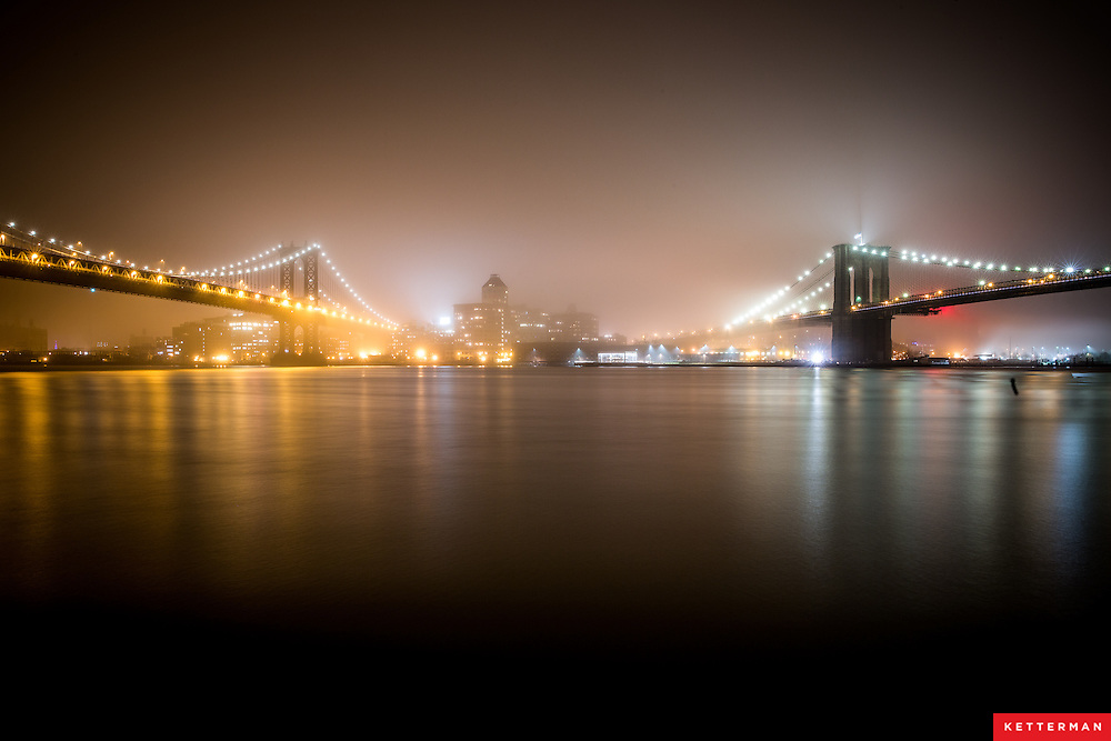 A heavy fog rolls across the East River looking in New York City. The Brooklyn Bridge and Manhattan Bridge were both hardly visible at times.