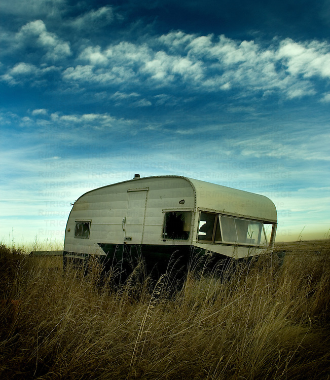 A small caravan in a field with long grass
