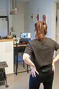 due to travel ban and social distancing, pilates classes are done remotely via Zoom or other video conferencing applications. Here a woman is following an instructor on her computer screen