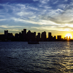 Boston sunset with Boston skyline and Boston Harbor sunset photo.  Boston Massachusetts is a major city along the Atlantic Ocean on the East coast of the United States.