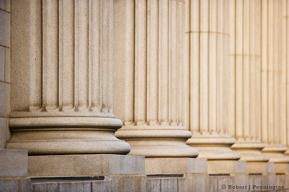 Receding stone columns in a row on a courthouse facade with narrow focus on the foreground.