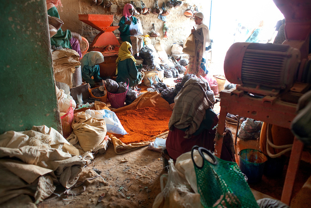 Bright orange ground Berberespice lies on the floor of the mill where women bring the ingredients to be ground, Mekelle
