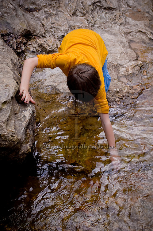 Child on search and discovery in a cool stream in Hanging Rock State Park in North Carolina