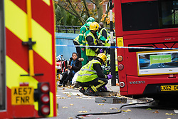Ladbroke Grove, London, November 17th 2016. A double decker bus crashes into Kensal House on Ladbroke Grove prompting a major response from the emergency services including the air ambulance. According to Detective Chief Superintendent Ellie O'Connor of Met Police Kensington and Chelsea, 14 people including the driver were hurt, with none sustaining life-threatening or life changing injuries. Police officers would not speculate on the cause of the accident, but apologised for delays and commended all branches of the emergency services for their prompt and efficient response. The bus will be towed away for further investigations. PICTURED: As paramedics and rescue crews work a woman stares at the camera.