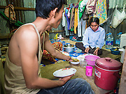 05 SEPTEMBER 2013 - BANGKOK, THAILAND:  A Cambodian family eats dinner in their dorm at the construction site of a new high rise apartment / condominium building on Soi 22 Sukhumvit Rd in Bangkok. The workers live in the corrugated metal dorms on the site. Most of the workers at the site are Cambodian immigrants.             PHOTO BY JACK KURTZ