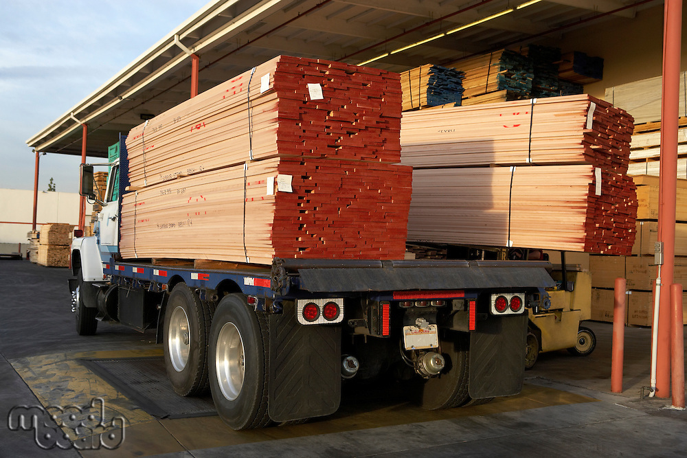 Stacks of Lumber Being Loaded onto Truck at Loading Dock